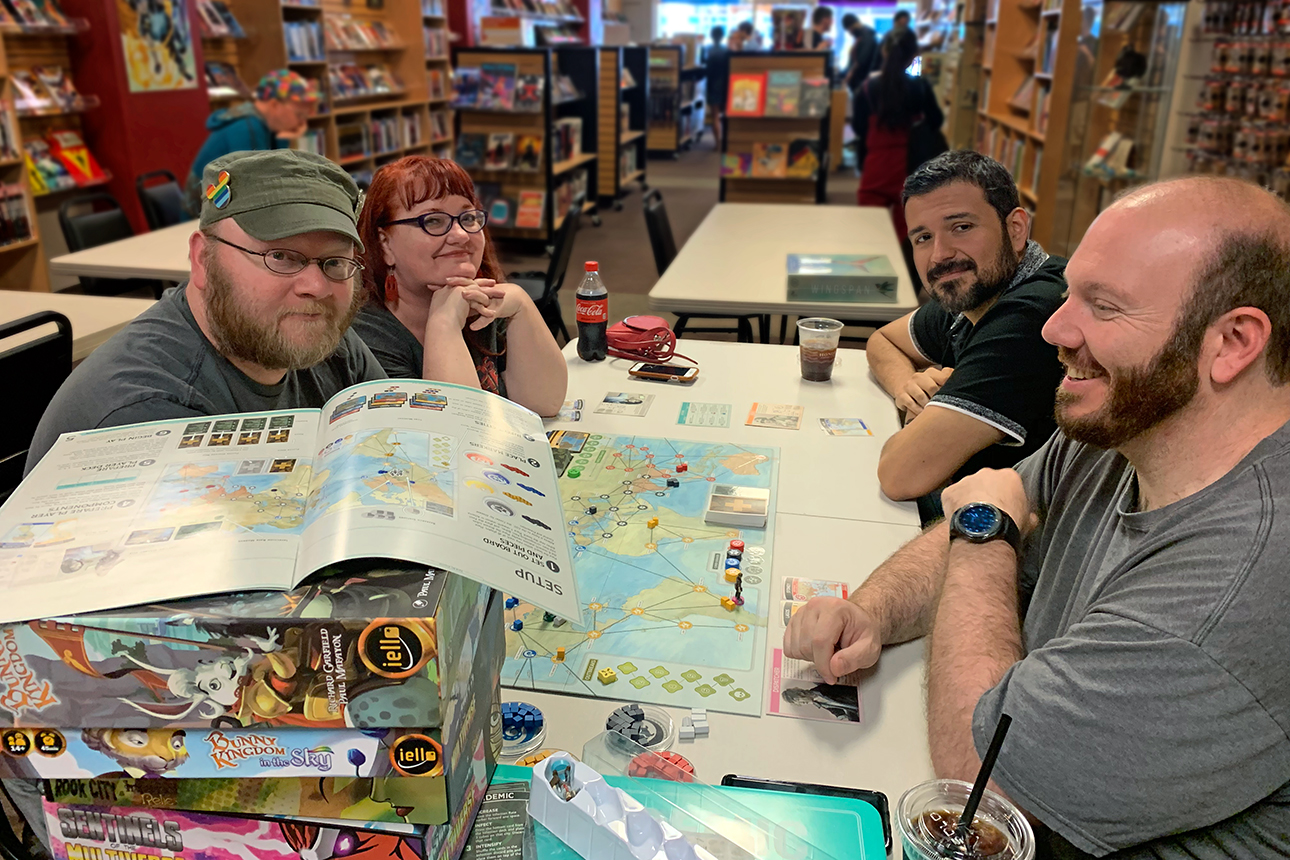 Four people gather around a table for board gaming