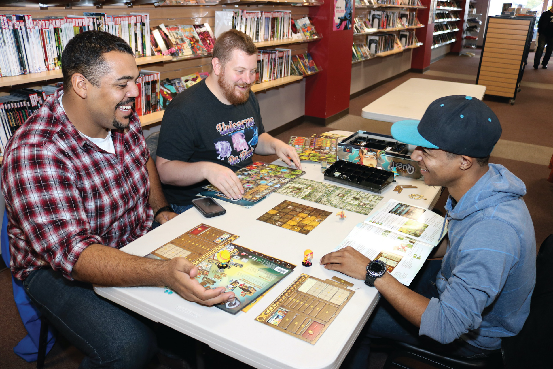 Three game players sit around a tabletop game inside a game shop
